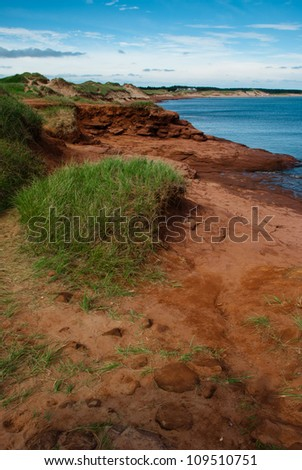 Grasses, red sand and rocks against blue water on PEI coast. - stock photo