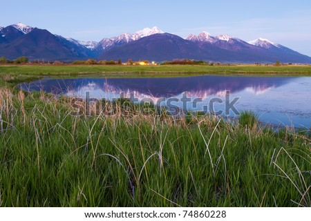 Grassy Meadow and Snow Capped Mountains Reflecting in Lake - stock photo