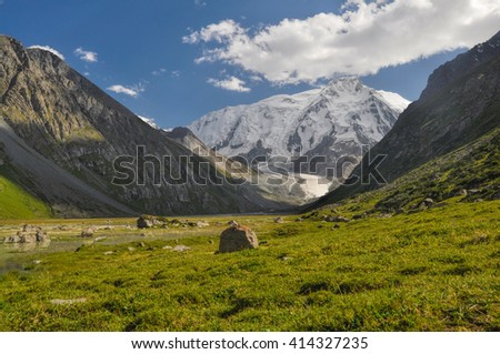 Grassy rocks lying in the valley under snow-covered Tien-Shan Mountains, Kyrgyzstan