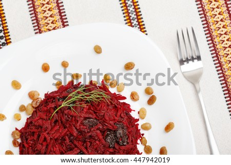 Grated beet salad with prunes and raisins, served on a white plate and home tablecloth with fork. Top view. low aperture shot, focus on beet and green - stock photo