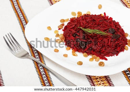 Grated beet salad with prunes and raisins, served on a white plate and home tablecloth with fork  - stock photo