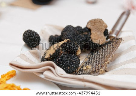 Grated black truffle on plate, close-up - stock photo