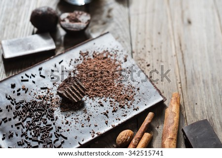 Grated cacao on top of chocolate bar with other ingredients around - stock photo