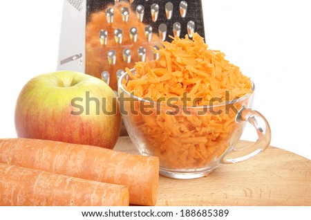 Grated carrots in a cup on a white background