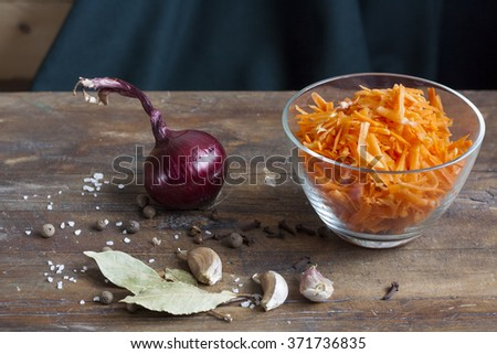 Grated carrots in bowl, spices and vegatables on wooden table. Selective focus. - stock photo