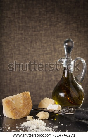 grated cheese, grated parmesan cheese with a grater and a jar and bottle of olive  oil