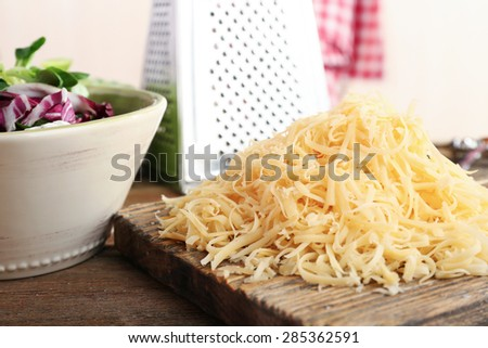 Grated cheese on wooden cutting board in kitchen - stock photo