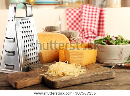 Grated cheese on wooden table on cutting board in kitchen - stock photo
