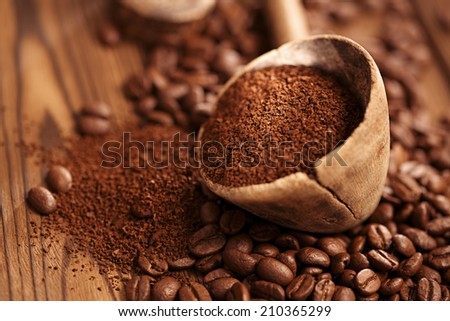 grated coffee in spoon on roasted coffee  beans background - stock photo