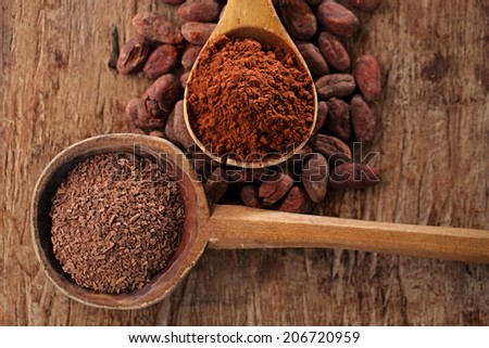 grated dark chocolate in old wooden spoon on roasted cocoa chocolate beans background - stock photo
