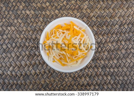 Grated mozzarella and cheddar cheese in white bowl over wicker background - stock photo