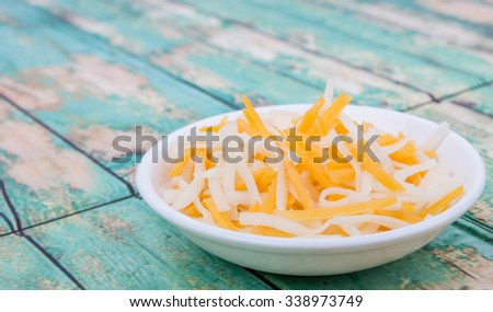Grated mozzarella and cheddar cheese in white bowl over wooden background - stock photo