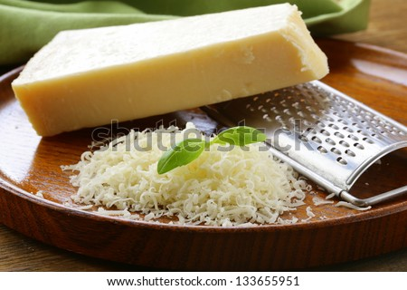 grated parmesan cheese and metal grater on wooden plate - stock photo
