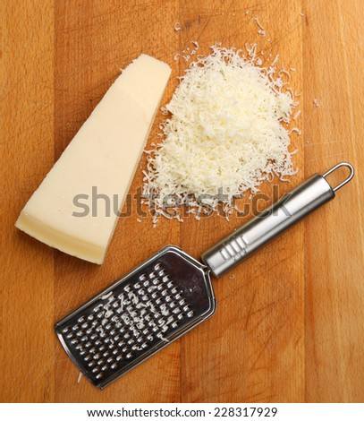 Grated Parmesan cheese on wooden chopping board. - stock photo