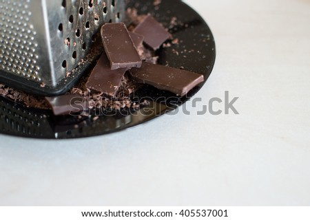 Grater and grated chocolate on a wooden table. - stock photo