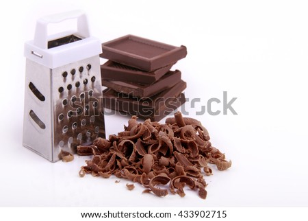 Grater, chocolate pieces and chips on a white background. - stock photo