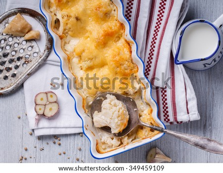 Gratin of cauliflower, potatoes and cheese in a ceramic form.selective focus - stock photo