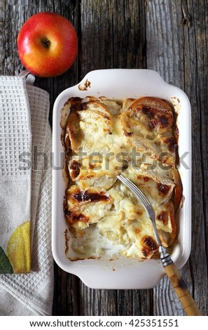 Gratin of potatoes, apples and  Camembert cheese on wooden table