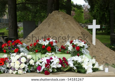 Grave covered with flowers right after funeral - stock photo