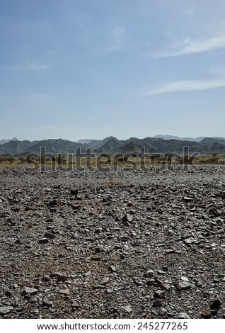 Gravel desert with mountains in background - stock photo