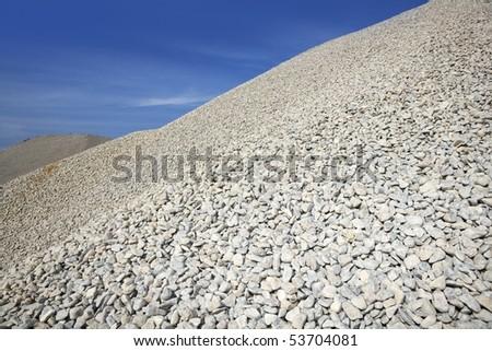 gravel gray mound quarry stock blue sky rolling stones - stock photo