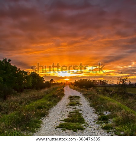 Gravel path with vibrant orange sunset. - stock photo