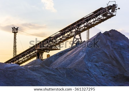 gravel pit with an industrial gravel sorter machinery at sunset - stock photo