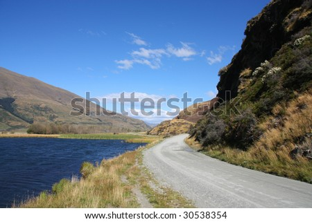 Gravel road and lake in Mount Aspiring National Park, New Zealand - stock photo