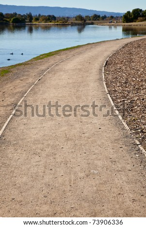 GRavel road in a park winding right from the lake shore. - stock photo