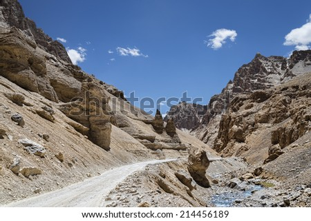 gravel road in mountains nearby river - stock photo