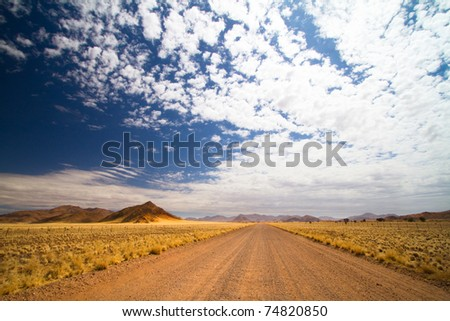 Gravel road in open spaces, Namibia - stock photo