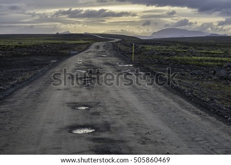 Gravel road in the highlands of southern Iceland, Road  is called kjalvegur. Jeep on the road in the distance. Dramatic skies and rough condition of the road
