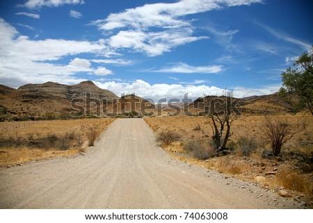 Gravel road in the region of Brandberg in Namibia - stock photo