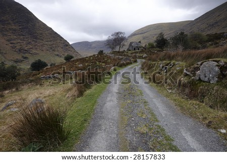 gravel road leading past derelict house in heart of Kerry Mountains, Co.Kerry, Ireland - stock photo