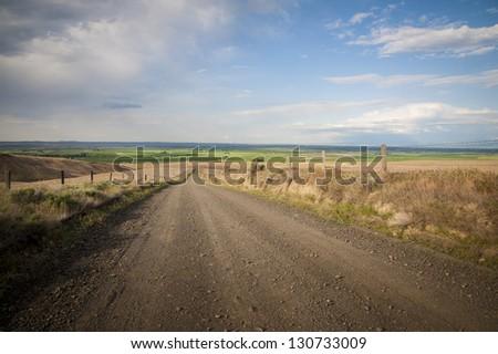 Gravel road through farmland in Washington state - stock photo