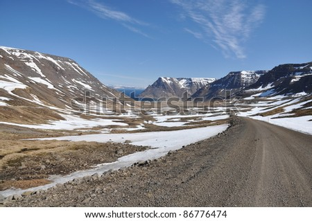 Gravel road to village in deep fjord, West fjord, Iceland - stock photo