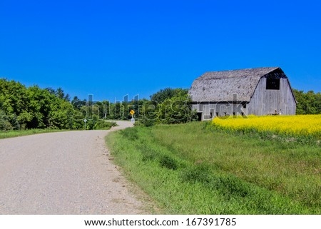 gravel road with view of a barn - stock photo