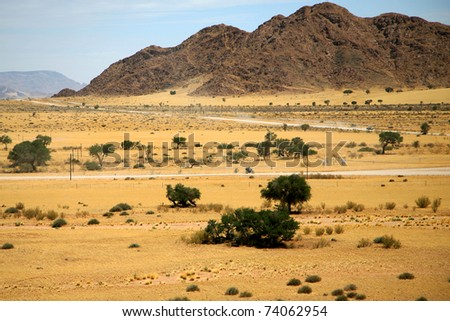 Gravel roads entering in Sossusvlei and a motor cycle driving alone - stock photo