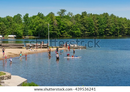 Gravenhurst Ontario June   Adults And Children Enjoying A Sandy Beach
