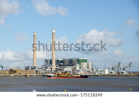 GRAVESEND, KENT, UK - FEB 4, 2014: Sand Fulmar, a trailing suction hopper dredge, sailing up the River Thames with Tilbury Power Station behind. - stock photo