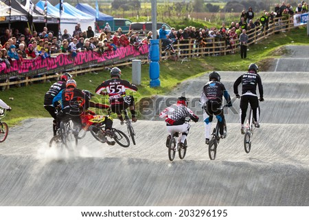 GRAVESEND, UK - APRIL 12: Riders competing in the elite class of the UK National BMX champs at the Kent cyclopark come together at the first jump during the final race on April 12, 2014 in Gravesend - stock photo
