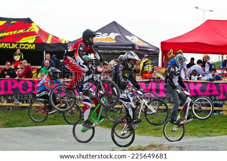 GRAVESEND, UK - APRIL 12: Riders competing in the elite class of the UK National BMX champs at the Kent cyclopark ride the rollers section during one of the heat races on April 12, 2014 in Gravesend  - stock photo