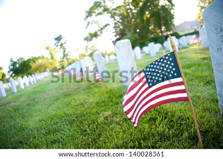 Gravesites at Arlington National Cemetery are decorated with flags in an annual Memorial Day tradition - stock photo