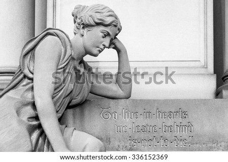 Gravestone and statue in cemetery with a meaningful message - stock photo