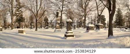 Gravestones shrouded in snow. - stock photo