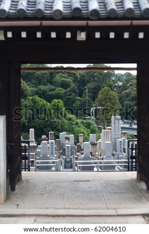 Gravestones through a gateway in Kyoto, Japan.