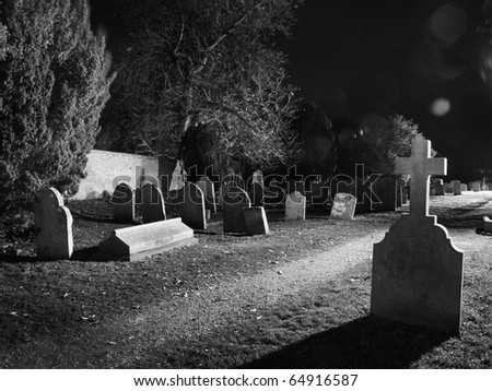 graveyard lit up at night time - stock photo