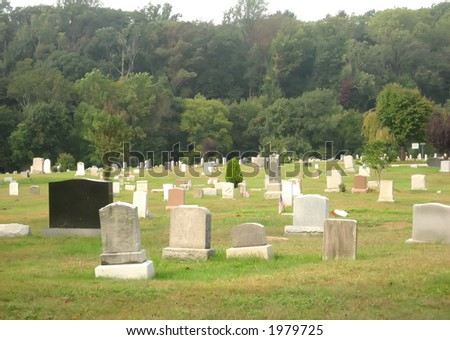 Graveyard next to forest in autumn. - stock photo