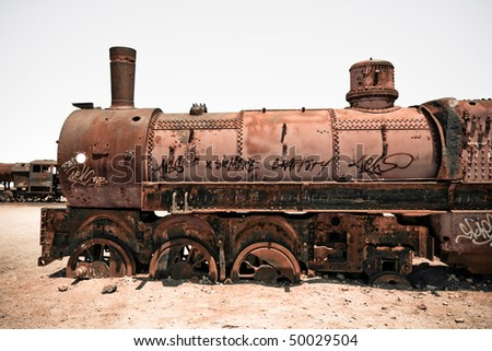 Graveyard of rusty old steam train in Bolivian desert - stock photo