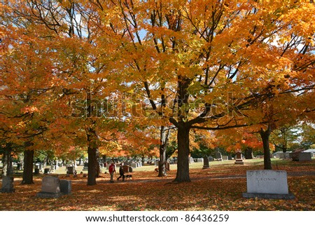 Graveyard with trees in golden foliage - stock photo